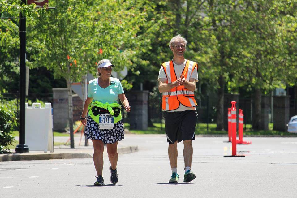How to Choose a Marathon, Course Marshal Walks with Race Participant